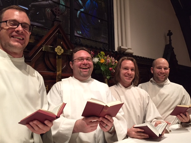 cantus firmus posing in hassocks holding hymnals