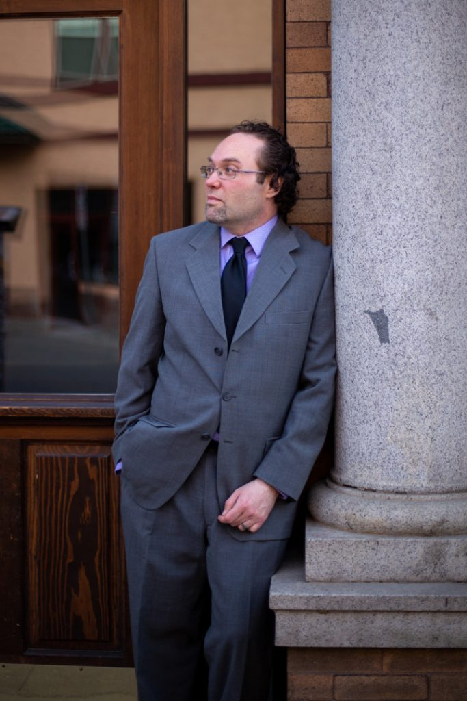 canadian composer ryan noakes leaning against a column