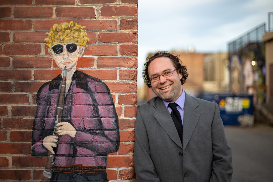 canadian composer ryan noakes posing beside a street mural of a clarinet player